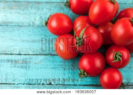 Cherry Tomatoes On Turquoise Wooden Table Top Texture. Fresh Seasonal Vegetables Concept