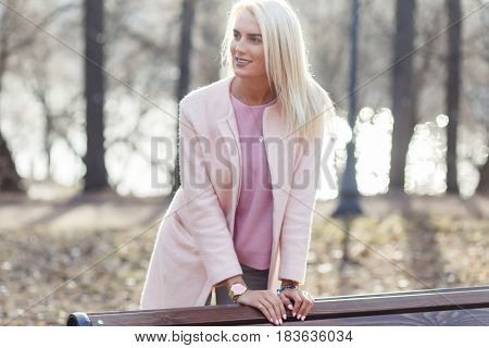 Long-haired blonde in coat at bench in woods