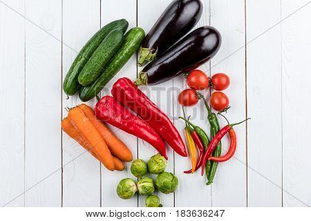Different Fresh Seasonal Vegetables On White Wooden Table Background