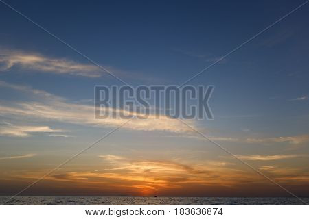 Scenic sky with clouds , setting sun over sea