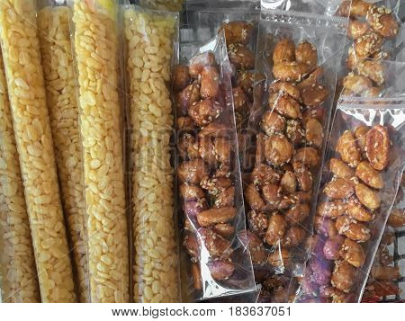 yellow mung beans and Roasted peanuts coated with sugar and sesame at asian street food market