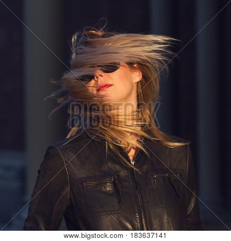 young Caucasian blonde woman with black sunglasses and waving hair wearing a black leather jacket natural light dark background motion blur