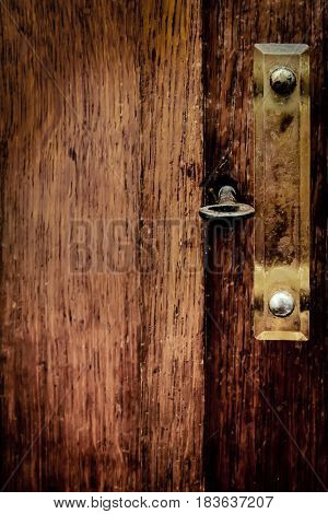 A fragment of an old wooden wardrobe with metal key in the keyhole and handle