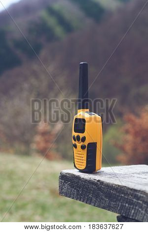 vertical side view of yellow walkie talkie with black antenna on a wooden bench and with trees grass and hills in the background