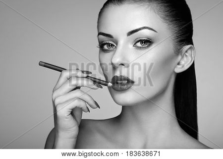Beautiful woman paints lips with lipstick. Beautiful woman face. Makeup detail. Beauty girl with perfect skin. Black and White photo