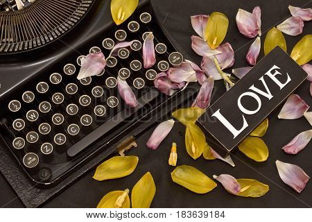 Antique old typewriter romantic style photo, petals of yellow and pink tulips, closeup, black leather background, A sign with the Word love, Nostalgic flat lay, still life