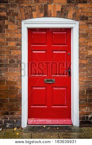 Red door with brick wall at England, UK.