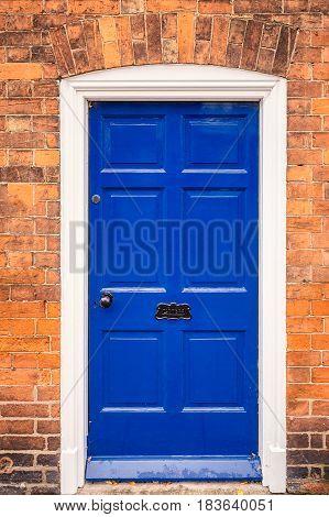 Blue door with brick wall at England, UK.