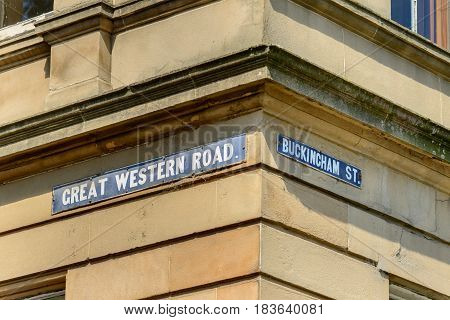 Street sign for Great Western Road and Buckingham Street sandstone residential building in the West End of Glasgow.
