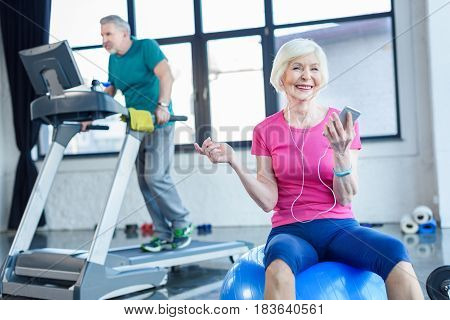Senior Sportswoman Sitting On Fitness Ball With Smartphone, Sportsman On Treadmill Behind In Senior