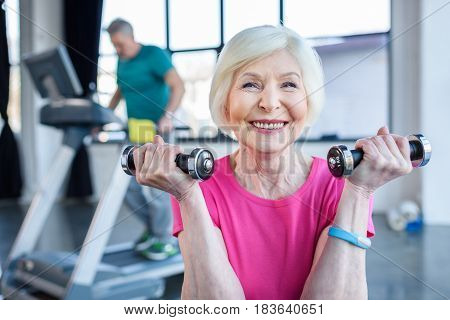 Senior Sportswoman Sitting On Fitness Ball With Dumbbells, Sportsman On Treadmill Behind  In Senior