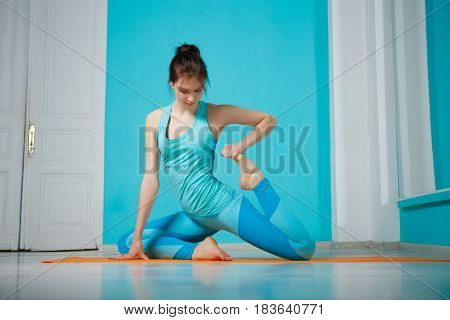 Athlete practicing yoga in gym on blue background