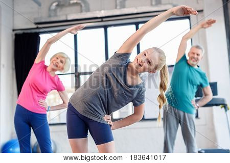 Happy Old Couple And Girl Exercising In Fitness Class For Kids And Senior People