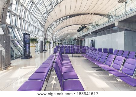 BANGKOK THAILAND - MARCH 7 2017 Interior of a modern airport a number of seats in the glassed-in room walkway for passengers boarding walkway in airport.