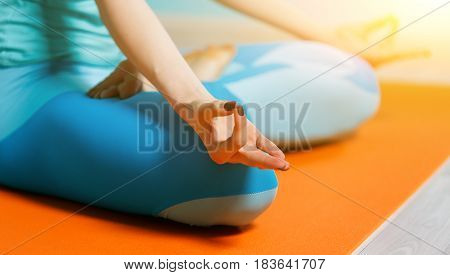 Young sportswoman in pose sitting on rug