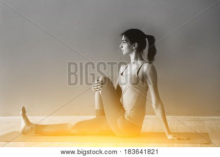 Black and white photo of sportswoman on rug in sports hall with aura effect