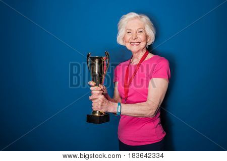 Happy Senior Sportswoman Holding Trophy Isolated On Blue