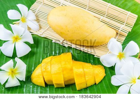 Yellow mango fruit with sliced mango on banana leaf