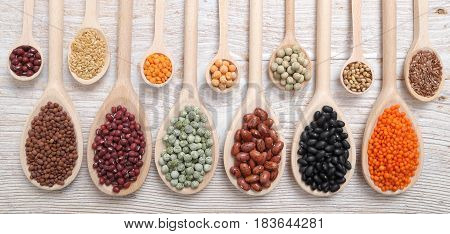 Lentils peas and beans on wooden spoons.