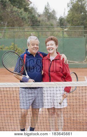 Senior Hispanic couple playing tennis