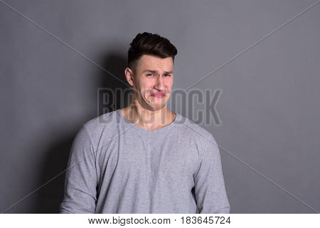 Negative human emotion. Man expressing disgust on face, grimacing on grey studio background