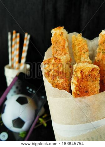 Crispy snacks in a paper bag for football match watching