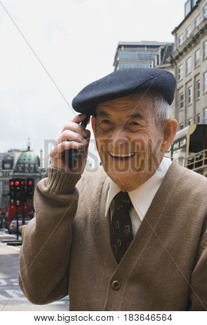 Senior Hispanic man in cap talking on cell phone