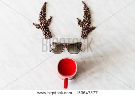 Deer. Horns from coffee beans. Sunglasses. Red cup