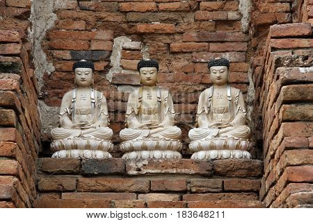 Ancient ruins of temple and three sculptures of Buddha in Ayutthaya in Thailand