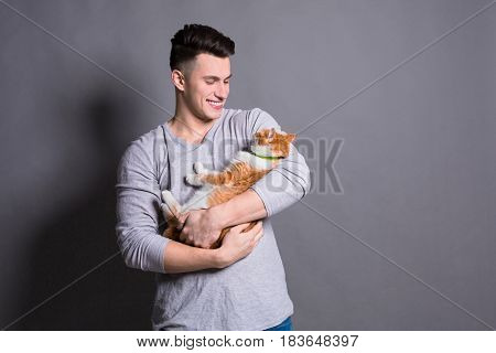 Young man with ginger cat. Pet care, positive emotion concept at gray studio background