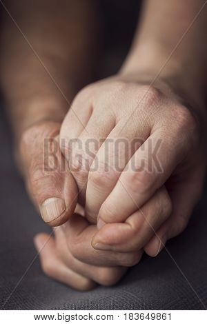 Old and young person holding hands. Elderly care and respect selective focus