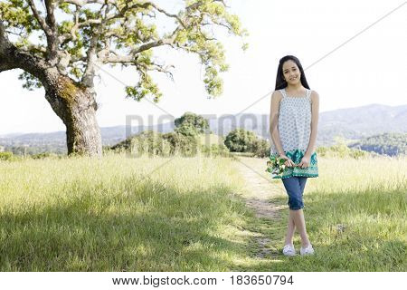 Hispanic girl standing in field