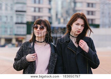 Two stylish young girls dressed in casual pose against the backdrop of the city on a sunny day