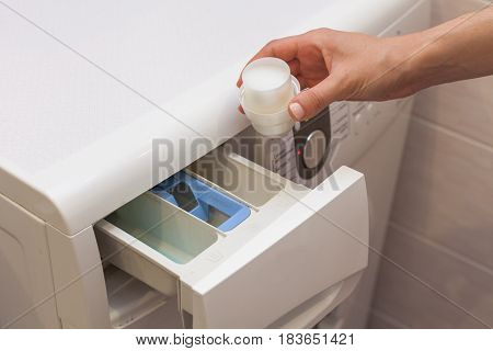 The girl pours detergent into the compartment with rinse aid