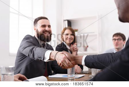 Business multiethnic handshake at office corporate meeting, contract conclusion and successful agreement concept. Modern businessman and other man's hands meet