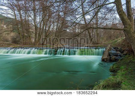 Water flowing over rocks in waterfall cascade in a forest in summer