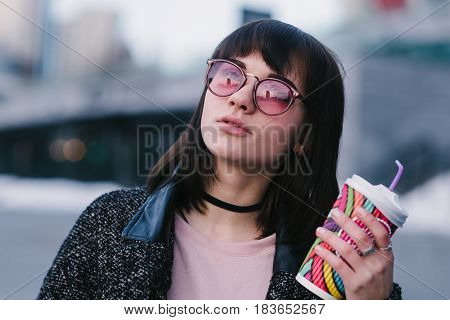 a young girl dressed in spring hipster pink glasses holding a colorful cup of hot drink