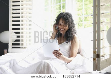 Black woman using digital tablet and talking on cell phone
