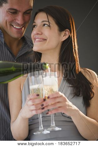 Smiling man pouring Champagne for girlfriend