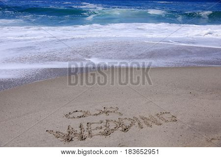 words Our Wedding written in the sand on the beach with the ocean tide and ocean waves