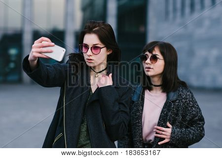 Portrait of two stylishly dressed girls doing selfie against the background of the urban landscape