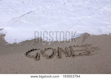 the word GONE written in the sand on the beach with the ocean tide and ocean waves