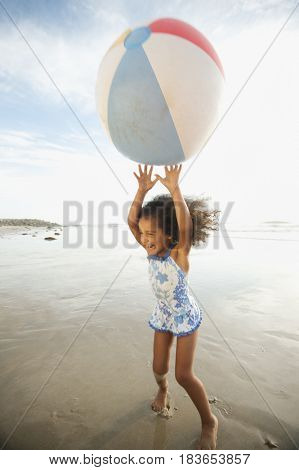 Mixed race girl playing with large ball on beach