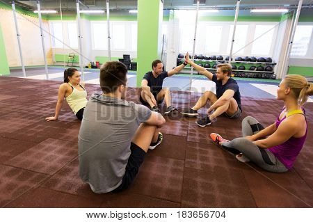 fitness, sport, exercising, gesture and healthy lifestyle concept - group of happy people resting and making high five in gym