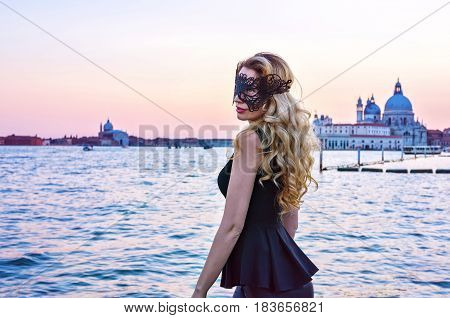 Portrait of a woman with a mysterious look at sunset in Venice. Girl wearing a black mask admiring the view at Grand Canal, Italy