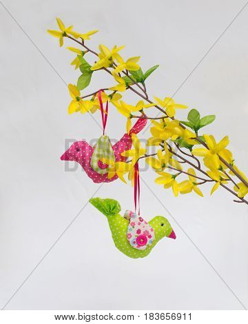 Two birds of fabric (handwork) on an artificial forsythia branch