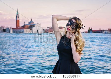 Portrait of a woman with a mysterious look at sunset in Venice. Blonde Girl wearing a black mask at Grand Canal, Italy