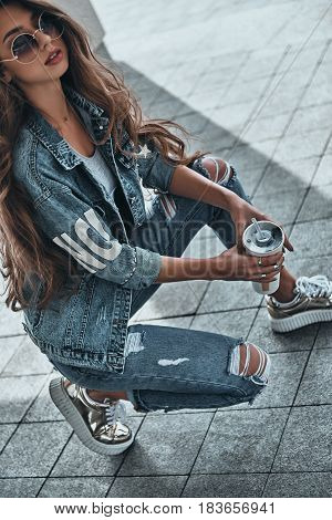 Carefree beauty. Attractive young woman in jeans wear holding a disposable cup while crouching outdoors