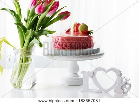 Pink romantic cake decorated with macaroons and strawberry. Delicious creamy cake with strawberies and macaroons on table closeup