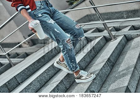 Carefree walk. Close-up of young woman in casual wear holding a disposable cup while walking down the stairs outdoors